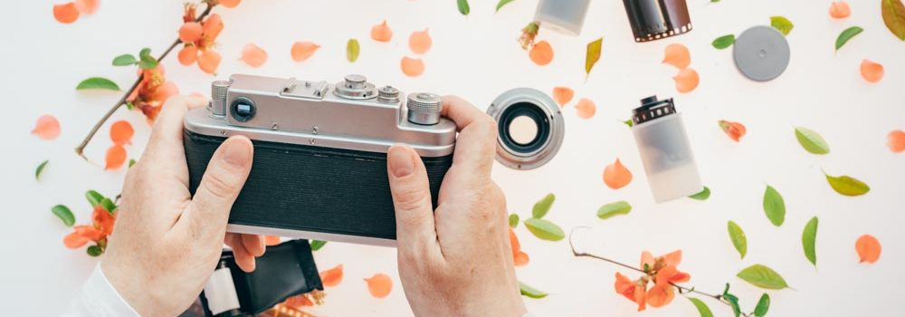 Woman holding vintage camera over springtime floral decoration, spring season is great for starting a new hobby like photography