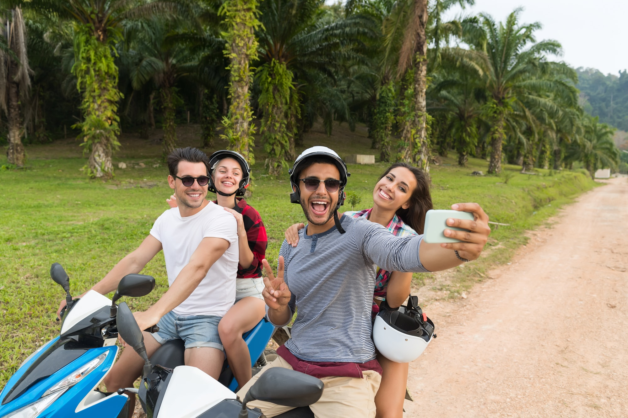 Two Couple Riding Motorbike, Man And Woman Taking Selfie Travel On Bike On Tropical Forest Road